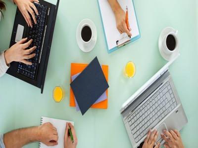 Green Desk with coffee, laptops, orange paper